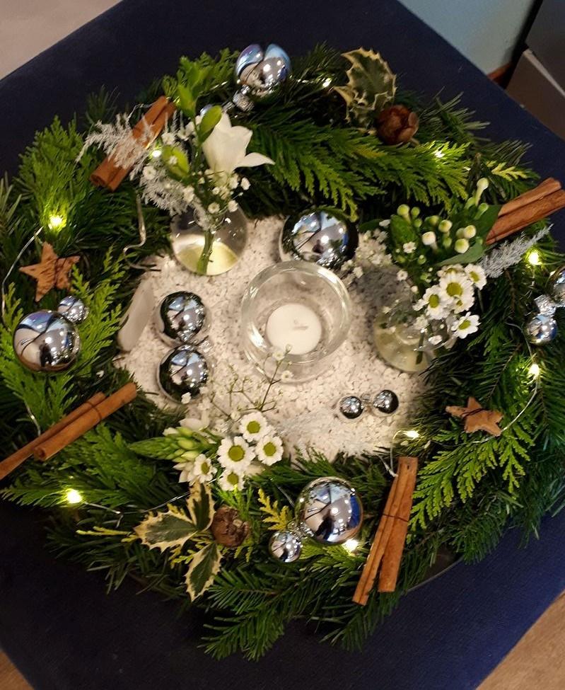 het betreft een kerstkrans met verse bloemen kerstversiering en kleine verlichting op batterijen